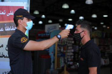 A Palestinian security guard takes the temperature of a visitor outside a mall in Gaza City on September 21, 2020. (Photo: Mahmoud Ajjour/APA Images)