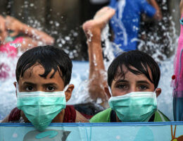Palestinian children wearing face masks cool off by playing in a pool in Gaza City on September 28, 2020. (Photo: Mahmoud Ajjour/APA Image)