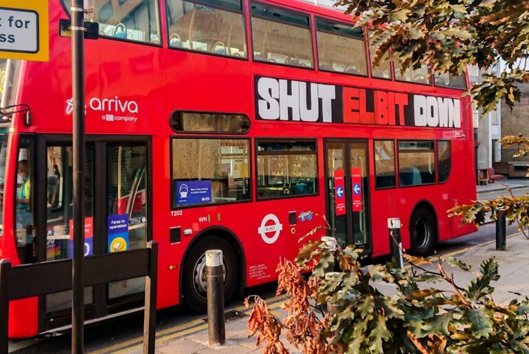 """A London bus was ad-hacked with """"Shut Elbit Down"""". Another previously travelled around London with """"Stop Arming Israel"""""""