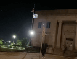 "Screenshot of someone spray painting ""Free Palestine"" beneath an Israeli flag outside of Temple Beth Hillel in Kenosha, WI."