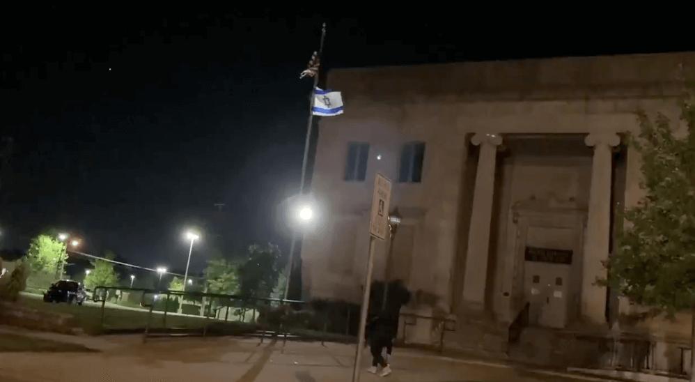 "Screenshot of someone spray painting ""Free Palestine"" beneath an Israeli flag outside of Temple Beth Hillel in Kenosha, WI."