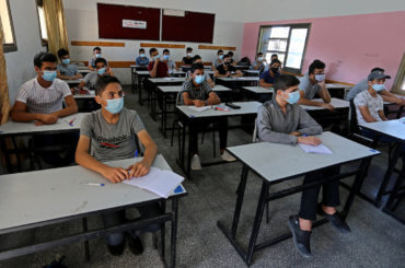 Palestinian students wearing face masks take part in a simulation of returning to schools, as a preventive measure to slow the spread of the coronavirus, organized by the Ministry of Education in Khan Younis in south Gaza on October 4, 2020. (Photo: Ashraf Amra/APA Images)