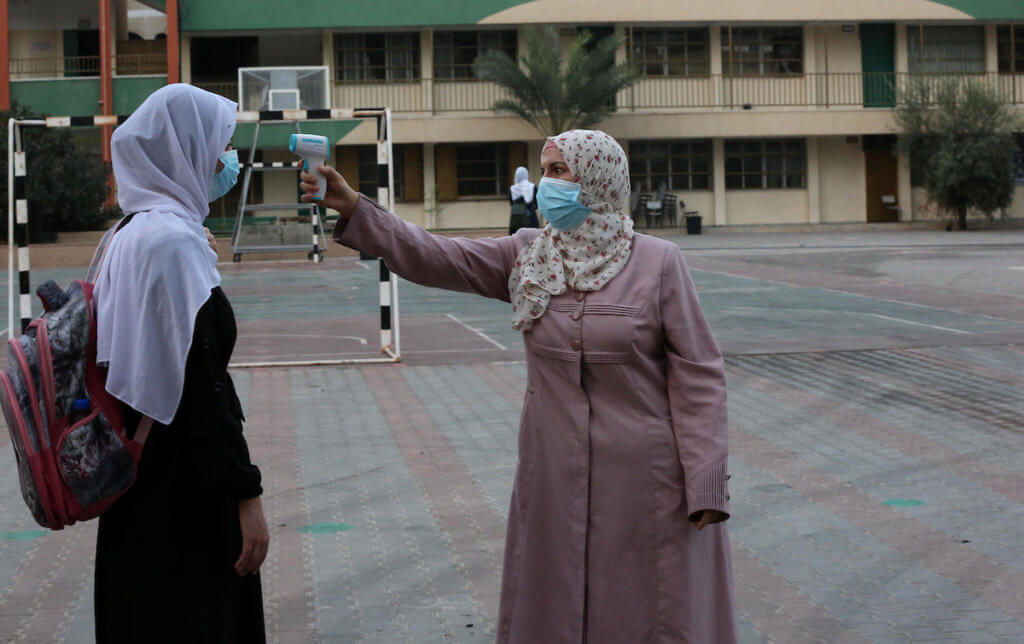 A Palestinian student has her temperature taken by a school staff member as schools partially reopened amid the coronavirus pandemic, in Khan Younis in the southern Gaza Strip on October 10, 2020. (Photo: Ashraf Amra/APA Images)