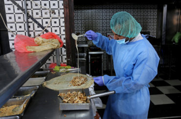 A Palestinian chef wears PPE as he prepare meals in a restaurant in Gaza City, on October 12, 2020. (Photo: Ashraf Amra/APA Images)