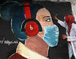 Palestinian artist paints a mural to raise awareness on wearing face masks amid the coronavirus pandemic in Gaza City on October 22, 2020. (Photo: Mahmoud Ajjour/APA Images)