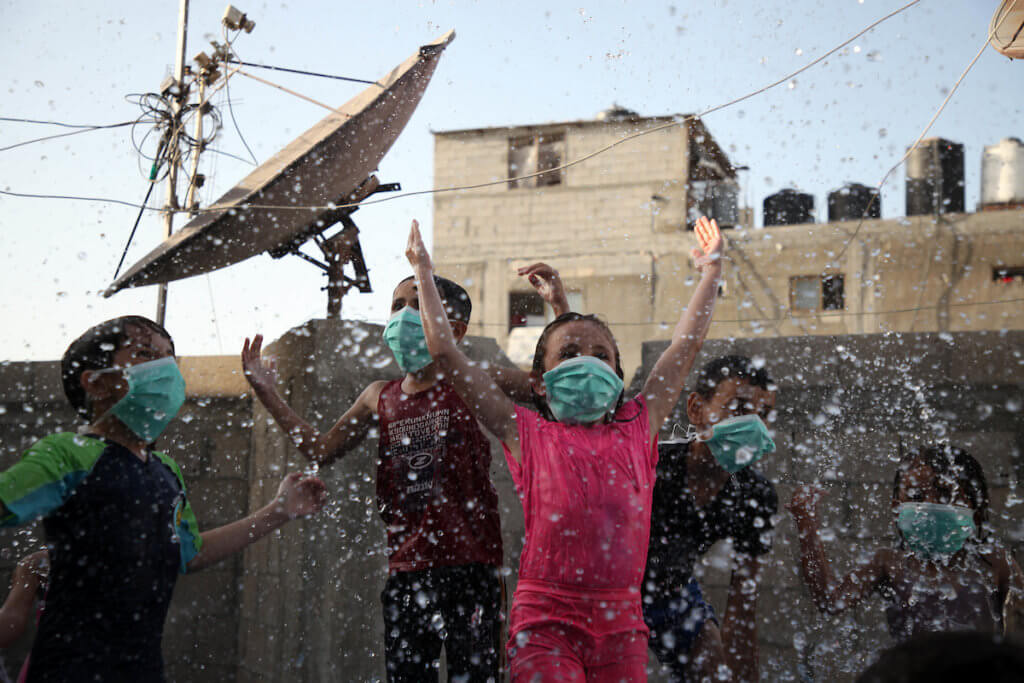 Palestinian children wearing face masks play together as they cool off in a pool erected on the rooftop of a residential building in Gaza City on September 28, 2020. (Photo: Mahmoud Ajjour/APA Images)