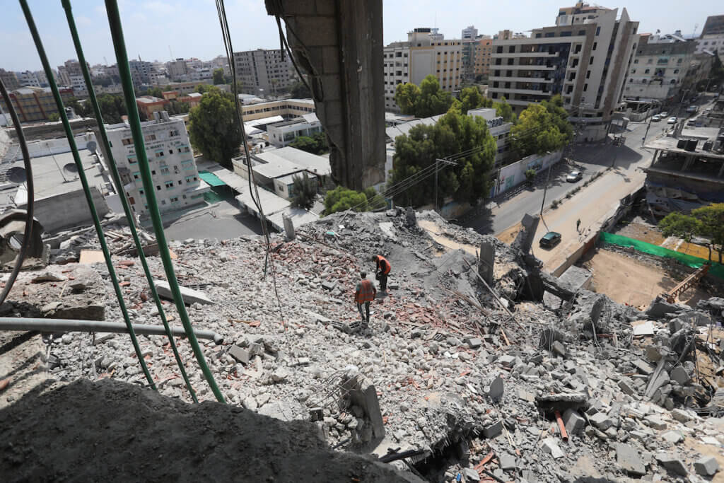 Palestinian workers remove the rubble of buildings recently destroyed by Israeli strikes in Gaza City on July 10, 2021. (Photo: Ashraf Amra/APA Images)