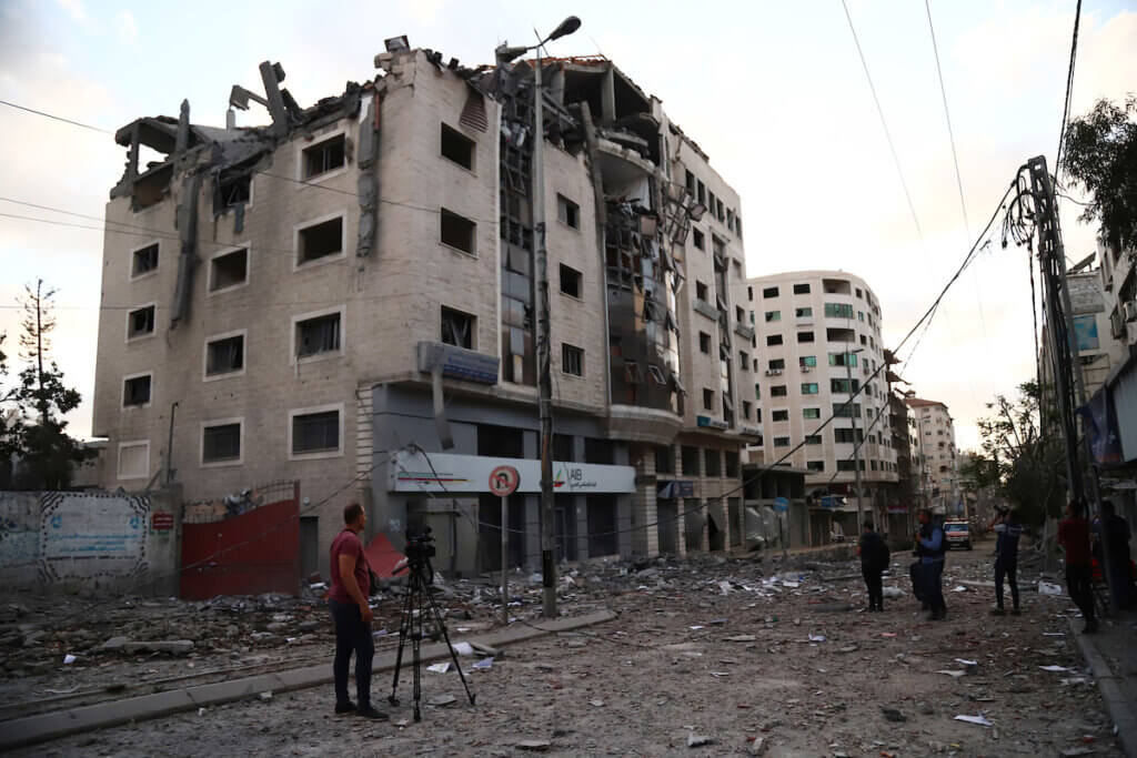Palestinians inspect the rubbles of a building after hit by an Israeli airstrike in front of ministry of health headquarters Gaza City on May 17, 2021. (Photo: Naaman Omar/APA Images)